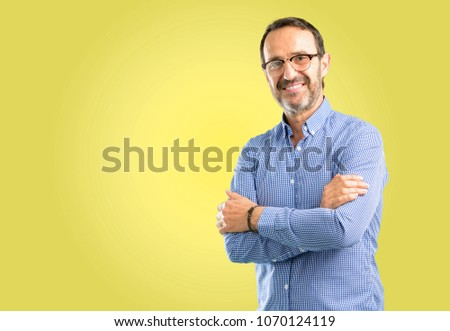 Handsome middle age man with crossed arms confident and happy with a big natural smile laughing #1070124119