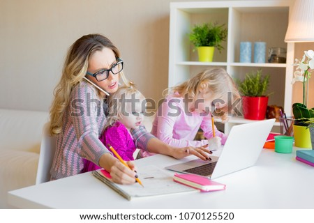 Busy woman trying to work while babysitting two kids Royalty-Free Stock Photo #1070125520
