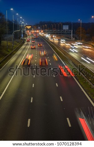 Fast moving traffic drives along the M42 in Warwickshire during evening rush hour, leaving traffic light trails as the vehicles are controlled using Active Traffic Management for each motorway lane #1070128394