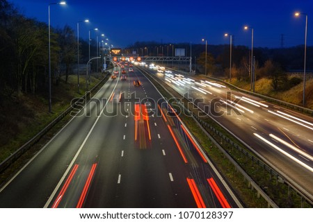 Fast moving traffic drives along the M42 in Warwickshire during evening rush hour, leaving traffic light trails as the vehicles are controlled using Active Traffic Management for each motorway lane #1070128397
