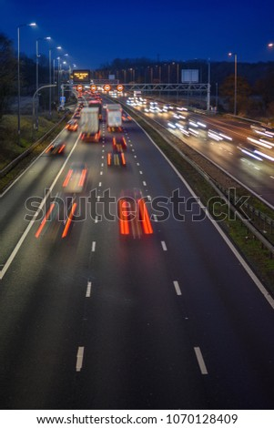 Fast moving traffic drives along the M42 in Warwickshire during evening rush hour, leaving traffic light trails as the vehicles are controlled using Active Traffic Management for each motorway lane #1070128409