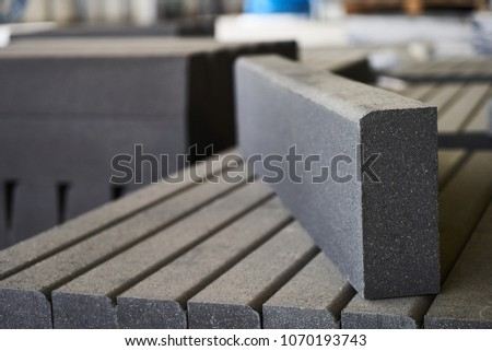 Concrete road curbs at the factory for the production of cement products, paving slabs, construction material for a new sidewalk #1070193743
