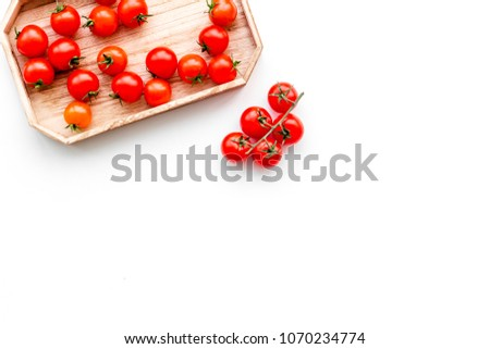 Fresh red cherry tomatoes in wooden tray on white background top view copy space #1070234774