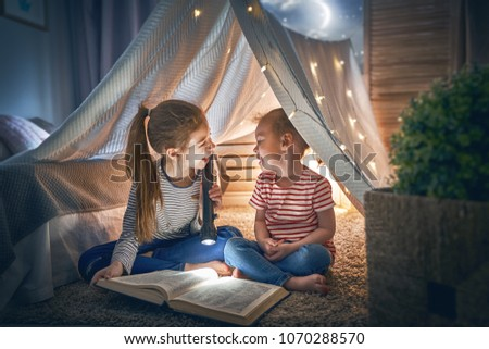 Two cute little children are reading a book with flashlights in tent. Happy girls playing at home. Funny lovely kids having fun in room.  #1070288570