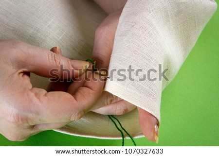 Closeup of hands with thread and needle sewing tools #1070327633