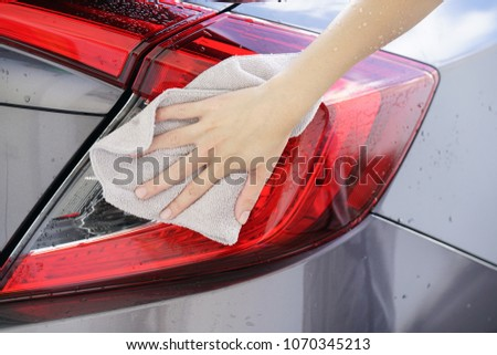 women hand dry wiping car surface with microfiber cloth after washing. #1070345213