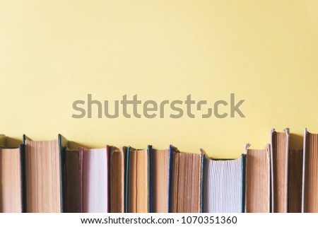 old books on a shelf with a yellow background #1070351360