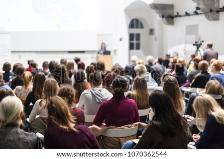 Female speaker giving presentation in lecture hall at university workshop. Audience in conference hall. Rear view of unrecognized participant in audience. Scientific conference event. #1070362544