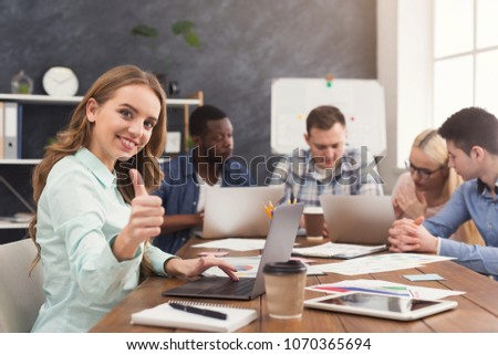 Business team talking about results of their work. Group of cheerful businesspeople discussing new marketing strategy, young woman showing thumb up to camera, copy space #1070365694