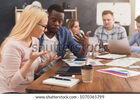 Serious business partners working in modern office. Two worried multiethnic coworkers discussing new project while working on laptop, copy space #1070365799