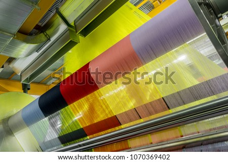 weaving loom at a textile factory, closeup. industrial fabric production line Royalty-Free Stock Photo #1070369402