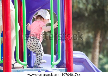 funny little girl on playground. playing child on slide #1070401766