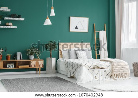 Bed between ladder and plant in green boho bedroom interior with grey carpet under lamps #1070402948