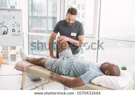 Rehabilitation therapy. Professional male therapist working in the rehabilitation center while doing the therapy Royalty-Free Stock Photo #1070432666