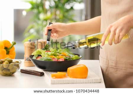 Woman dressing fresh vegetable salad with olive oil in kitchen Royalty-Free Stock Photo #1070434448