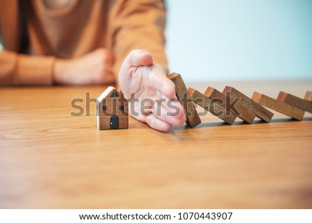 Woman hand stopping risk the wooden blocks from falling on house, Home insurance and security concept. Royalty-Free Stock Photo #1070443907