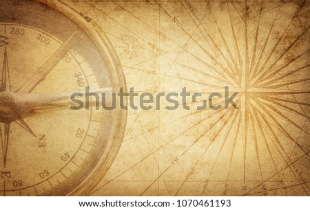 Old vintage retro compass on ancient map. Survival, exploration and nautical theme grunge background #1070461193