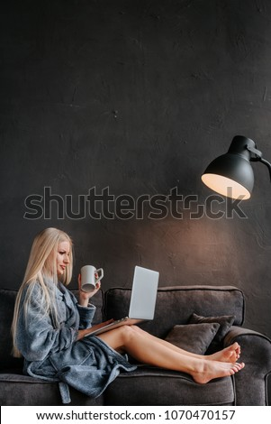 Happy young woman is relaxing on comfortable couch and using laptop at home.Sexy blonde woman typing on laptop in sofa, online flirt.Woman relaxing at home after bath with laptop and cup of tea.