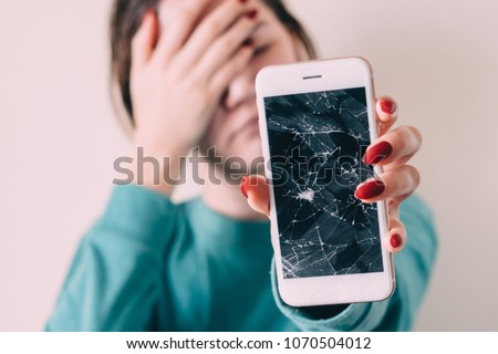 Broken glass screen smartphone in hand of upset girl, white background. Royalty-Free Stock Photo #1070504012