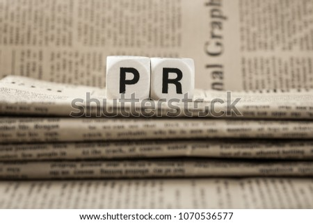 Abbreviation PR on newspapers background #1070536577