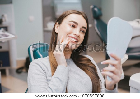 The girl smiles in dentistry. patient dentist racing model at the Dental Clinic. White well-groomed teeth after taking a doctor. Tooth whitening and tooth enamel. In the hands of the mirror #1070557808