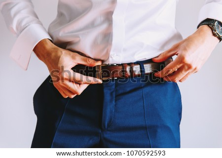 A man in blue pants and a white shirt buttoned a brown leather trouser belt. He has a watch on his hand Royalty-Free Stock Photo #1070592593