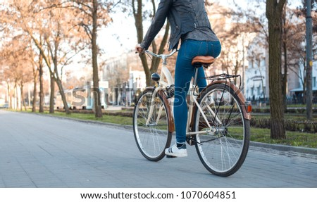 A girl in a leather jacket and jeans rides a bicycle along the avenue in the spring #1070604851