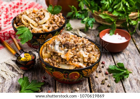 Traditional buckwheat porridge with meat and vegetables in bowl on wooden background. Selective focus. #1070619869