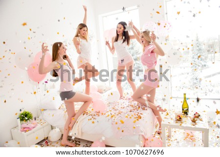 Cheerful slim pretty charming funky girls in rain of colorful stars confetti enjoying meeting indoor drinking alcohol dancing shouting screaming laughing with raised arms jumping on sleepover patty #1070627696