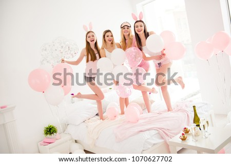 Portrait of pretty, cheerful, charming, attractive, cool, funky girls chilling indoor, enjoying meeting, posing, raised legs, looking at camera, having air balloons, laughing on sleepover party #1070627702