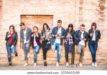 Friends group using smartphone against wall at university college backyard break - Young people addicted by mobile smart phone - Technology concept with always connected millennials - Filter image #1070633189