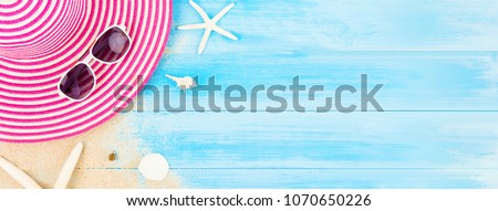 Colorful summer holiday beach banner background with accessories on light blue wood panel, border design on top view with copy space #1070650226