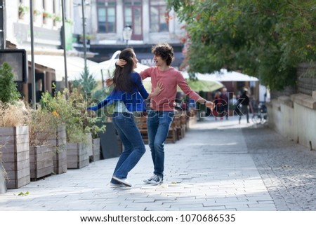 Lovely couple dancing West Coast Swing in the streets, carefree and happy. #1070686535