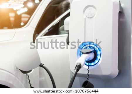 Power supply for electric car charging. Electric car charging station. Close up of the power supply plugged into an electric car being charged. #1070756444