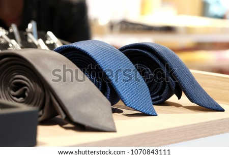 selective focus at blue necktie. Roll up necktie on the table and blur background . Concept of gentleman and necktie fashion, Shopping , father's day. #1070843111
