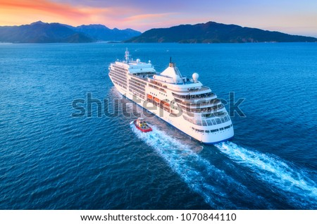 Cruise ship at harbor. Aerial view of beautiful large white ship at sunset. Colorful landscape with boats in marina bay, sea, colorful sky. Top view from drone of yacht. Luxury cruise. Floating liner #1070844110