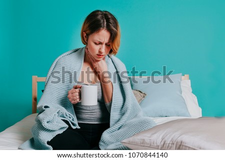 Woman sore throat with glass of water in her bed. Blue background Royalty-Free Stock Photo #1070844140