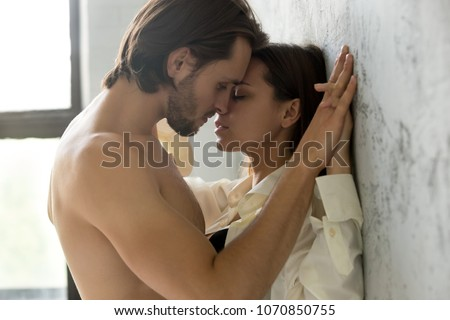 Beautiful young sensual couple holding hands leaning on wall, loving millennial affectionate  man and woman getting closer to kiss each other teasing enjoying tenderness and intimacy, feeling desire #1070850755