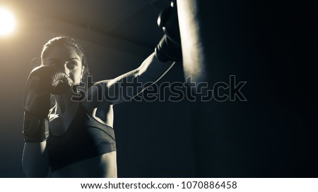 Young woman doing boxing training at the gym, she is wearing boxing gloves and hitting the punching bag #1070886458