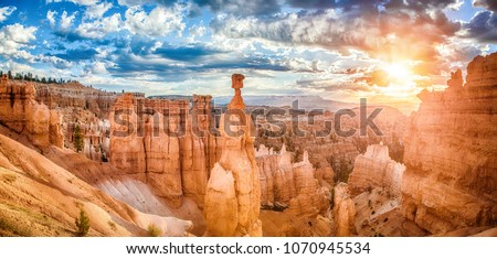 Panoramic view of amazing hoodoos sandstone formations in scenic Bryce Canyon National Park in beautiful golden morning light at sunrise with dramatic sky and blue sky, Utah, USA Royalty-Free Stock Photo #1070945534