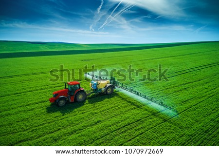 Aerial view of farming tractor plowing and spraying on field. #1070972669