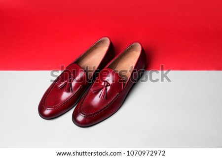 Red stylish loafers. Red and white paper background. #1070972972