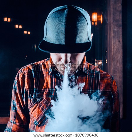 Punk hipster man in the vape shop is sitting at the bar and smoking a mechanical vape device. Toned image. The concept of popularization of vaping and vape shops. Cap view square cropping #1070990438