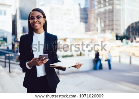 Half length portrait of cheerful african american student of faculty of lawyer dressed in formal wear holding folder and smartphone device in hands standing in downtown in urban setting #1071020009