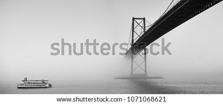 Ferry boat crossing under a suspension bridge in Halifax, Nova Scotia in thick fog.  Royalty-Free Stock Photo #1071068621