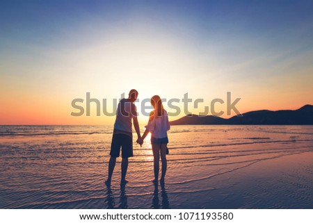 couple hand hold on the beach between sunset. #1071193580