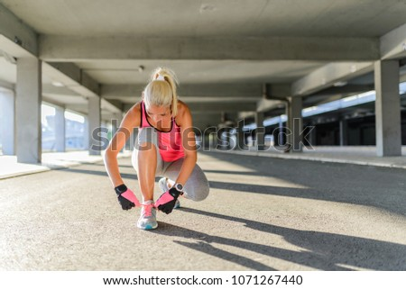 Unrecognizable young runner tying her shoelaces #1071267440