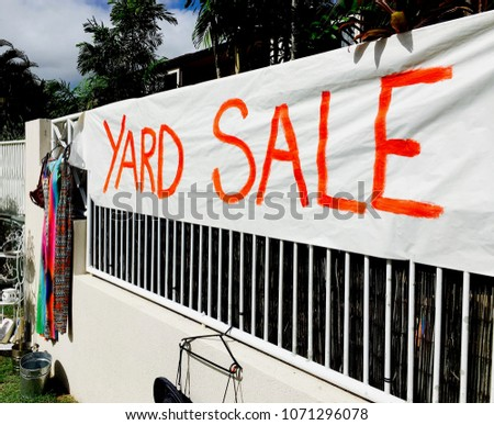 Yard sale painted sign attached to a fence