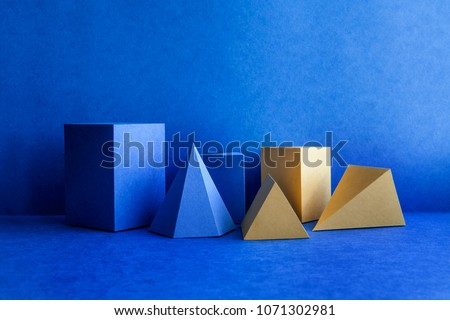 Geometrical figures still life composition. Three-dimensional blue yellow prism pyramid tetrahedron rectangular cube objects on blue background. Platonic solids figures, simplicity concept photography Royalty-Free Stock Photo #1071302981