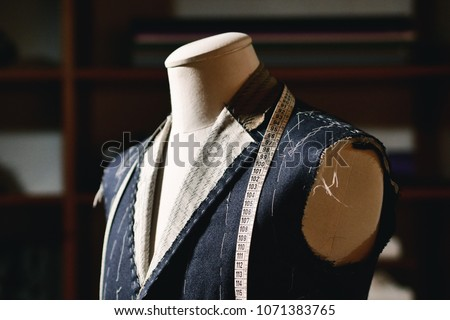 Close up of a suit hanging on hanging clothes, just made to measure by a tailor in his tailoring #1071383765